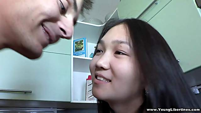 An Asian teen gets her shaved pussy fucked in a kitchen